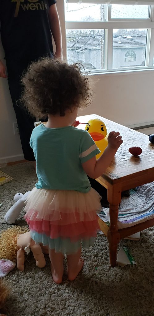 A curly-haired toddler wearing a tulle skirt paints the eyebrow of a very large rubber duckie.