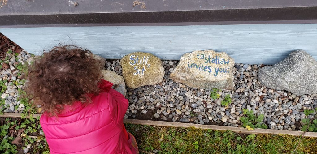 """A toddler in a pink coat bends down to investigate two rocks, one of which is painted with """"Still, sit."""" and the other """"tastatlaw invites you."""""""