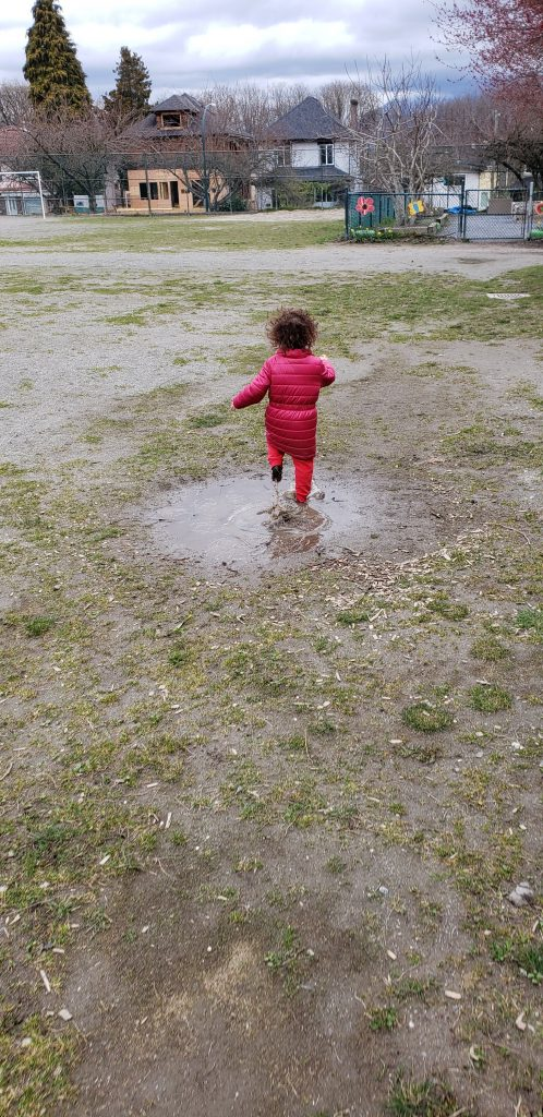 A toddler in a pink coat runs in a mud puddle in only her sock feet.