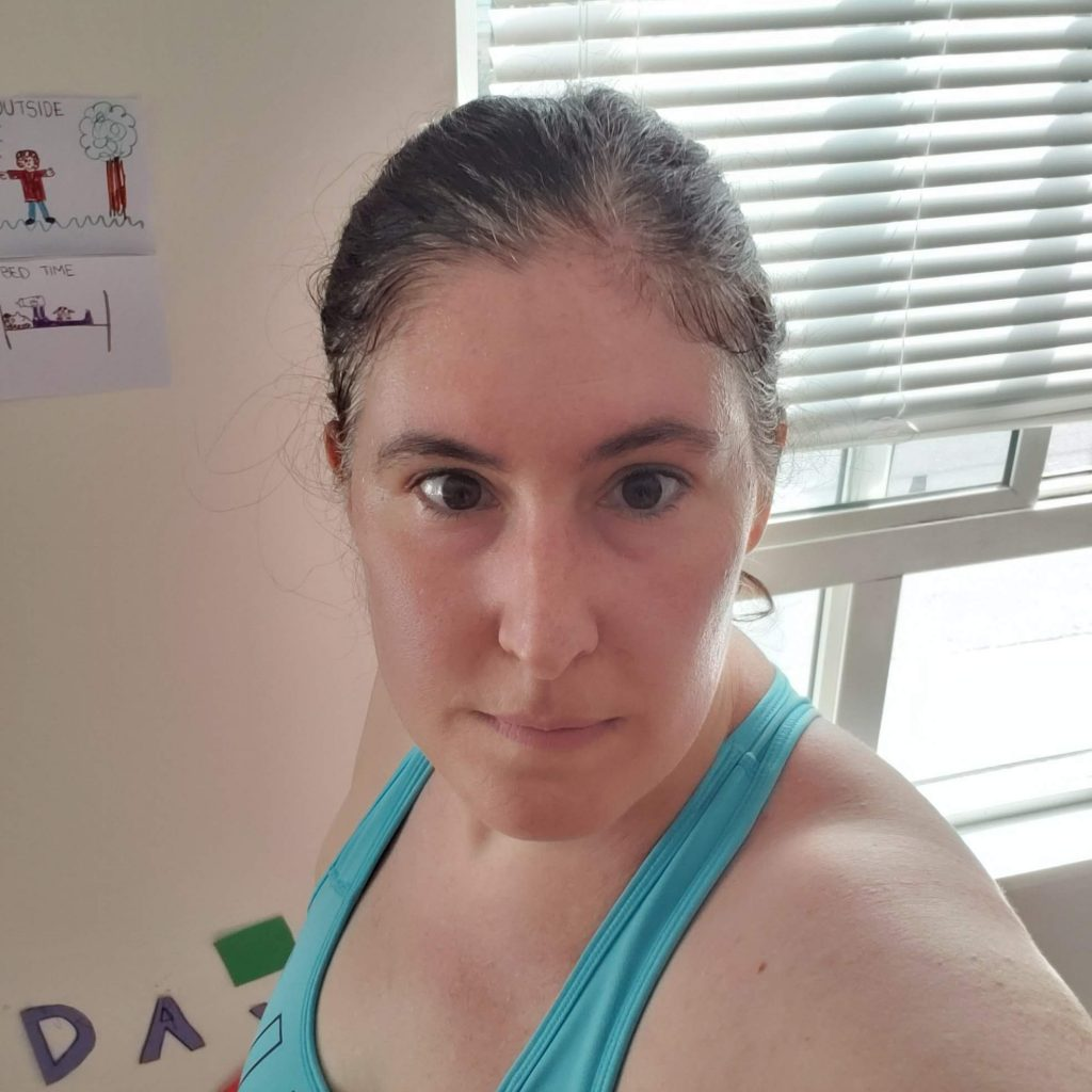 Arley taking a post-workout selfie in a blue sports bra
