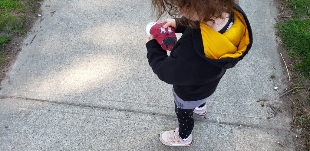 A toddler in a black and yellow hoodie holds a rock that's been painted maroon with a face on it.
