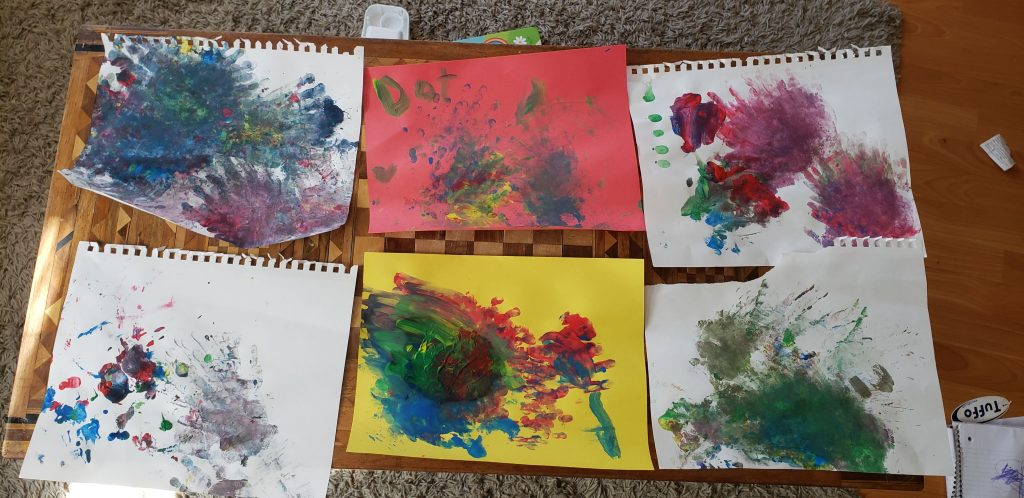 Six toddler drawings laid on a table.