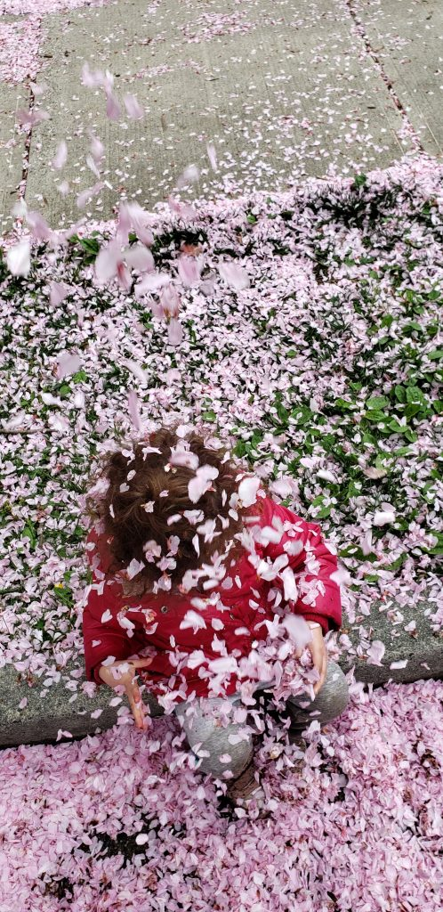 A toddler in a pink coat covered in blossoms