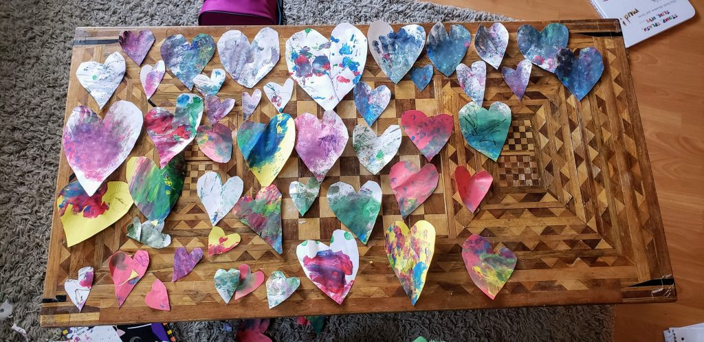Multi-coloured hearts laid out on a table.